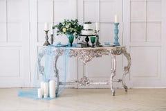 Härligt dekorera tabellen med stearinljus och bröllopstårtan i studio royaltyfria foton