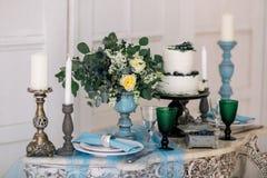 Härligt dekorera tabellen med stearinljus, vasen med blommor och bröllopstårtan på tabellen i studio royaltyfri bild