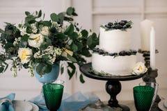 Härligt dekorera tabellen med stearinljus, vasen med blommor och bröllopstårtan på tabellen i studio arkivbild