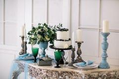 Härligt dekorera tabellen med stearinljus, vasen med blommor och bröllopstårtan på tabellen i studio arkivfoto
