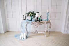 Härligt dekorera tabellen med stearinljus, vasen med blommor och bröllopstårtan på tabellen i studio royaltyfria foton
