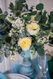 Härligt dekorera tabellen med vasen med blommor på tabellen i studio arkivbilder