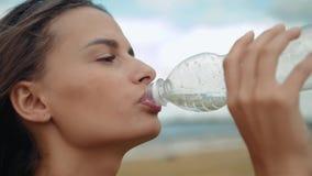Härligt dricksvatten för den unga kvinnan för konditionidrottsman nenbrunetten efter utarbetar att öva på solnedgångaftonsommar i lager videofilmer