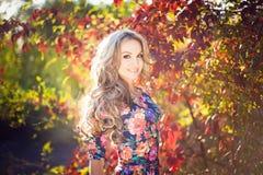 Härligt elegant ungt blont kvinnaanseende i en parkera i autu Royaltyfri Fotografi