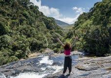 Härligt europeiskt kvinnaanseende med händer upp nära floden i bergen arkivfoton