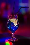 Härligt exponeringsglas med en coctail på stången på tabellen Nattklubb Alkoholdryckblått färgar med en citron på insidan Arkivbild