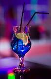 Härligt exponeringsglas med en coctail på stången på tabellen Nattklubb Alkoholdryckblått färgar med en citron på insidan Royaltyfri Foto