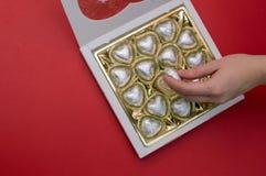 Härligt förälskelsebegrepp för valentindag Den kvinnliga handen som tar sötsaken från sötsakerna, boxas Royaltyfri Fotografi