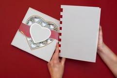 Härligt förälskelsebegrepp för valentindag Romantisk ask av sötsaker och den moderna anmärkningsboken med kvinnlighänder på det r Fotografering för Bildbyråer