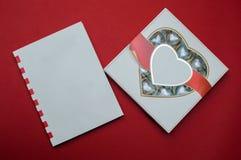 Härligt förälskelsebegrepp för valentindag Romantisk ask av sötsaker och den moderna anmärkningsboken på den röda bakgrunden Fotografering för Bildbyråer