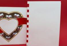 Härligt förälskelsebegrepp för valentindag Romantisk ask av sötsaker och den moderna anmärkningsboken på den röda bakgrunden Arkivfoto