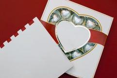 Härligt förälskelsebegrepp för valentindag Romantisk ask av sötsaker och den moderna anmärkningsboken på den röda bakgrunden Royaltyfri Bild