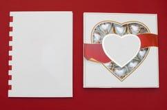 Härligt förälskelsebegrepp för valentindag Romantisk ask av sötsaker och den moderna anmärkningsboken på den röda bakgrunden Arkivbilder
