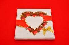 Härligt förälskelsebegrepp för valentindag Romantisk ask av sötsaker på den röda bakgrunden Arkivfoton