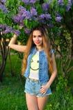 Härligt flickaanseende bredvid en blommande Bush av lilan royaltyfri fotografi