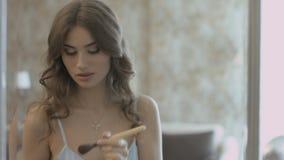 Härligt flickaanseende för spegeln och applicera pulvret på framsidan genom att använda en borste stock video