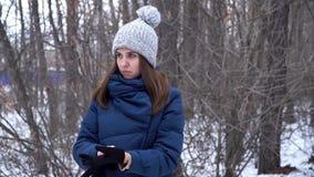 Härligt flickaanseende i vinterskogen och bärande handskar, snöig filialbakgrund ovanför skogliggande skjuten snowtreesvinter lager videofilmer