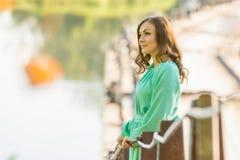 Härligt flickaanseende på bron över floden och blickar in i avståndet arkivfoto