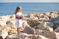 Härligt flickaanseende på den steniga kusten Royaltyfri Foto