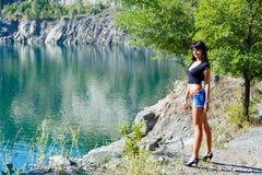 Härligt flickaanseende på kusten av en bergflod Royaltyfri Bild