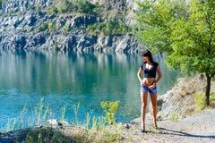 Härligt flickaanseende på kusten av en bergflod Arkivbilder