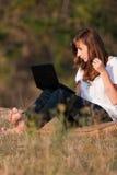 Härligt flickaarbete på datoren Arkivbild