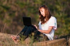 Härligt flickaarbete på datoren Royaltyfri Fotografi