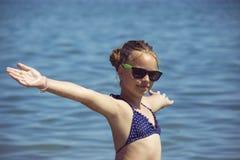 Härligt flickaleende med lyftta händer, kvinna på strandsommarsemester begrepp av frihetsloppet royaltyfri foto