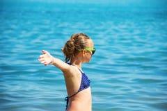 Härligt flickaleende med lyftta händer, kvinna på strandsommarsemester begrepp av frihetsloppet Royaltyfri Bild