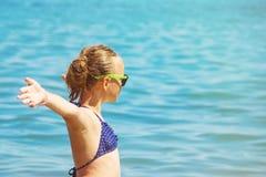 Härligt flickaleende med lyftta händer, kvinna på strandsommarsemester begrepp av frihetsloppet arkivbild