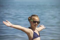 Härligt flickaleende med lyftta händer, kvinna på strandsommarsemester begrepp av frihetsloppet royaltyfri fotografi