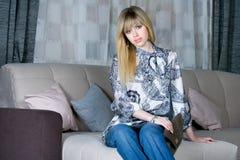 Härligt flickasammanträde på en soffa fotografering för bildbyråer