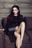 Härligt flickasammanträde på en soffa i ett landshus Royaltyfri Bild