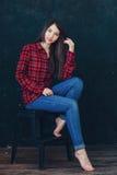 Härligt flickasammanträde på en stol Fotografering för Bildbyråer