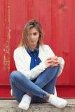 Härligt flickasammanträde på jordningen nära väggen i jeans och en vit blus, hennes hår framkallar vind Royaltyfri Bild