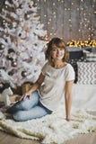 Härligt flickasammanträde på mattan nära julgranen 720 Arkivfoton