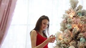 Härligt flickaslut som dekorerar upp en julgran i inre stock video