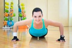 Härligt göra för kvinna skjuter upp övning i idrottshall Arkivfoton