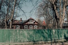 Härligt gammalt hus bak ett förfallet grönt trästaket royaltyfria bilder