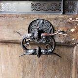 Härligt gammalt järn- dörrhandtag på en gammal skalande dörr i Prague royaltyfri bild