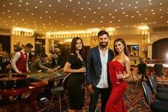 Härligt glamourfolk som ler mot i kasinopokerroulett arkivbild