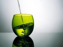 Härligt grönt exponeringsglas av vatten, hälla som plaskar Arkivfoto