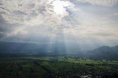Härligt grönt fält med solljus som kommer till och med moln royaltyfria foton