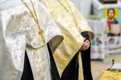 Härligt guld- kors i manliga händer av prästen som bär den guld- ämbetsdräkten på ceremoni i kristen domkyrkakyrka, helig sakrame arkivfoto