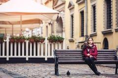 Härligt höstflickasammanträde på bänk i mitt av gatan på kafébakgrund Royaltyfri Fotografi