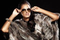 Härligt ha på sig för brunettlady pälsfodrar och solglasögon. Arkivfoton