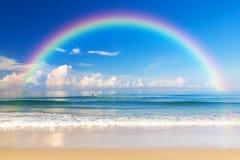 Härligt hav med en regnbåge i himlen arkivbild