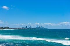 Härligt hav med mjuka vågor och cityscape på bakgrunden Royaltyfri Foto