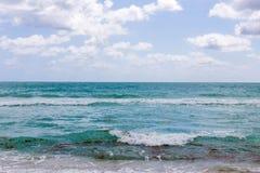 Härligt hav med vågor och turkosvatten för molnig himmel på stranden på en sommardag royaltyfria foton