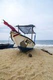 Härligt havssiktslandskap med fiskarefartyget strandade på den sandiga stranden Arkivbilder